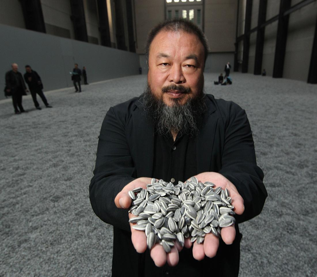 LONDON, ENGLAND - FILE:  Chinese Artist Ai Weiwei holds some seeds from his Unilever Installation 'Sunflower Seeds' at The Tate Modern on October 11, 2010 in London, England. Chinese state radio reported on June 22, 2011 that the Chinese artist Ai Weiwei has been freed on bail after confessing to tax evasion. Ai was detained on April 3, 2011 and is reported to be in poor health.  (Photo by Peter Macdiarmid/Getty Images)