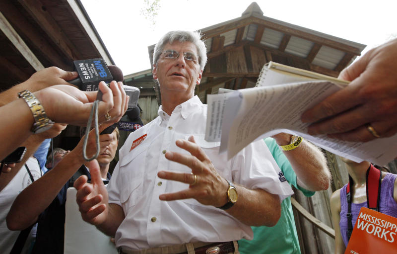 Gov. Phil Bryant speaks with reporters following his morning address at the Neshoba County Fair in Philadelphia, Miss., Thursday, Aug. 2, 2012. The fair is a traditional gathering place for fairgoers, politicians, area residents, business leaders and voters.  (AP Photo/Rogelio V. Solis)