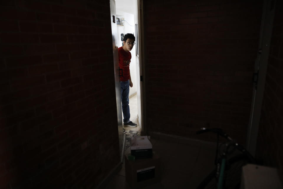 A young man quarantined in his apartment with symptoms consistent with COVID-19, opens the door to receive a delivery of medical and food supply kits dropped off by city workers, in the Coyoacan district of Mexico City, Thursday, April 9, 2020. To help halt the spread of the new coronavirus, the Mexican megalopolis is making home deliveries to households with a symptomatic person, providing kits containing food staples, face masks, gloves, antibacterial gel, paracetamol, a thermometer, and benefits cards with a balance of 1000 pesos (around $42). (AP Photo/Rebecca Blackwell)
