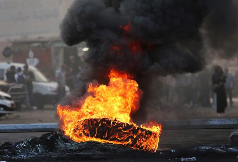 Demonstrators stand near burning tires blocking a street during a protest targeting the government over an economic crisis, in Nabatiyeh