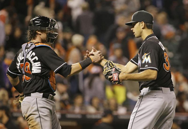 Miami Marlins relief pitcher Steve Cishek, right, is greeted by catcher Jarrod Saltalamacchia, left, at the end of a baseball game against the San Francisco Giants Friday, May 16, 2014, in San Francisco. Miami won the game 7-5. (AP Photo/Eric Risberg)