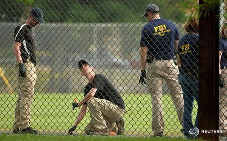 FBI technicians examine playing field at scene of shooting of Congressional baseball practice