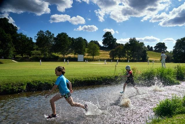 Children play in the River Tillingbourne on the weekend recreational cricket was allowed to resume. The waterway forms a natural boundary at Abinger Cricket Club in Surrey. Worplesdon and Burpham were the visitors on a sunny day in July