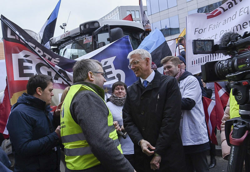 Latvian Prime Minister Krisjanis Karins, center right, speaks with farmers from the Baltic's as they demonstrate outside of an EU summit in Brussels, Thursday, Feb. 20, 2020. Baltic farmers on Thursday were calling for a fair allocation of direct payments under the European Union's Common Agricultural Policy. (AP Photo/Riccardo Pareggiani)