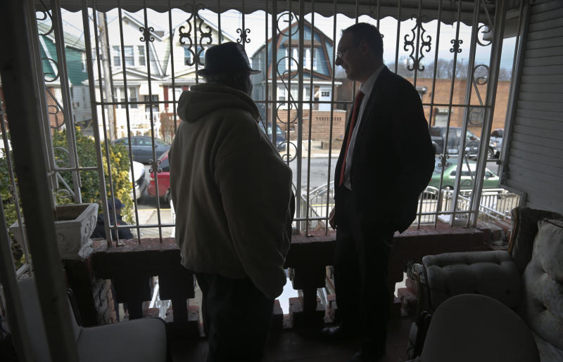 In this Feb. 1, 2017, photo, Raymond Murray gets a visit from his lawyer, Robert Seewald, right, at his home in New York. Murray is the victim of deed theft, a foreclosure fraud where older people are mostly the target. (AP Photo/Bebeto Matthews)