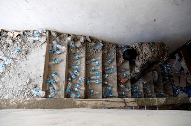 <p>A fighter of Syrian Democratic Forces places empty plastic bottles on stairs of a building at their positions, at the frontline in Raqqa, Syria, Oct. 6, 2017. (Photo: Erik De Castro/Reuters) </p>