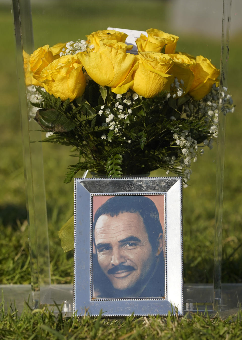 A portrait of the late actor Burt Reynolds sits in front of flowers during a ceremony featuring the unveiling of a memorial sculpture of Reynolds at Hollywood Forever Cemetery, Monday, Sept. 20, 2021, in Los Angeles. Reynolds died in 2018 at the age of 82. (AP Photo/Chris Pizzello)