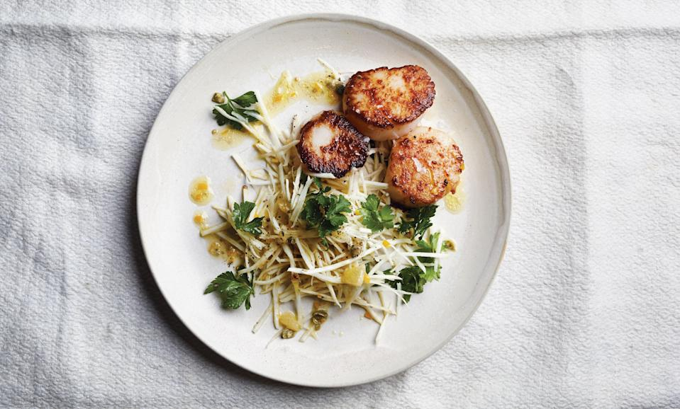 """Pick a small to medium celery root and peel off its hide with a sharp knife. Inside you'll find ivory-green flesh that's crisp, a bit nutty, and utterly delicious in salads. This take on a classic remoulade provides perfect contrast to the silken luxury of seared scallops. <a href=""""https://www.bonappetit.com/recipe/sea-scallops-celery-root-salad?mbid=synd_yahoo_rss"""" rel=""""nofollow noopener"""" target=""""_blank"""" data-ylk=""""slk:See recipe."""" class=""""link rapid-noclick-resp"""">See recipe.</a>"""