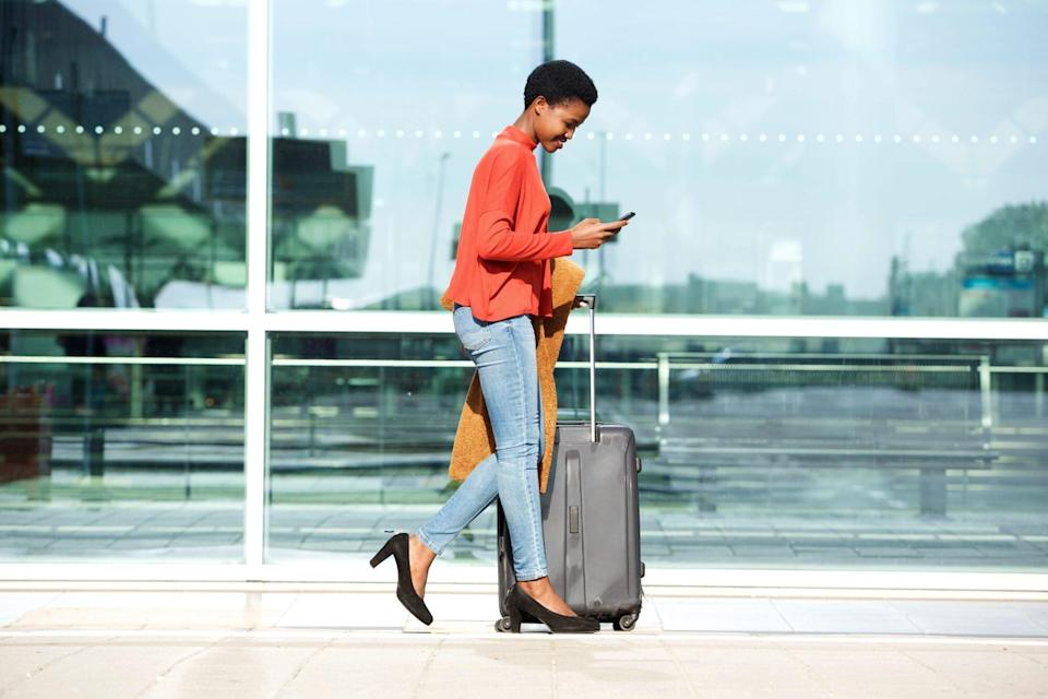 woman walking outside airport with luggage