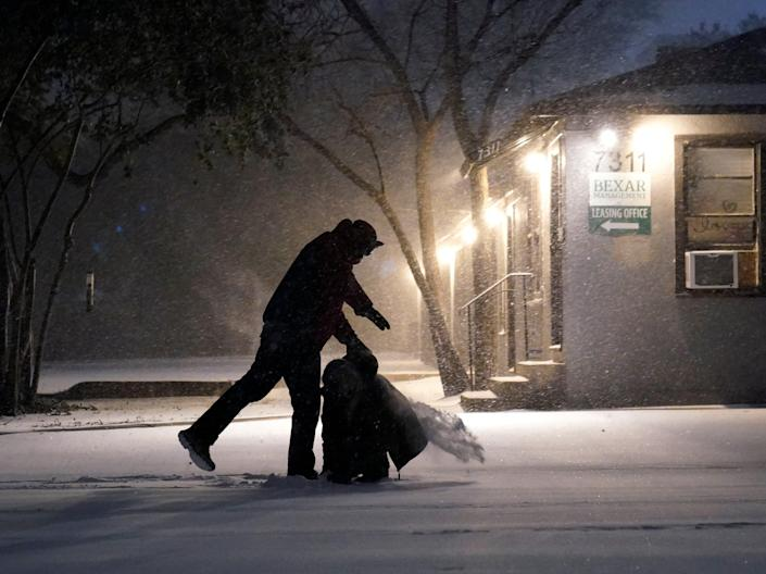 <p>Two people play in the snow in San Antonio, on 14 February 2021</p> ((Associated Press))