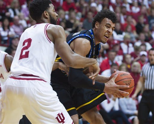 Coppin State's Zach Burnham grimaces as he takes the ball into the lane against Indiana's Christian Watford during the first half of an NCAA college basketball game Saturday, Dec. 1, 2012, in Bloomington, Ind. (AP Photo/Doug McSchooler)