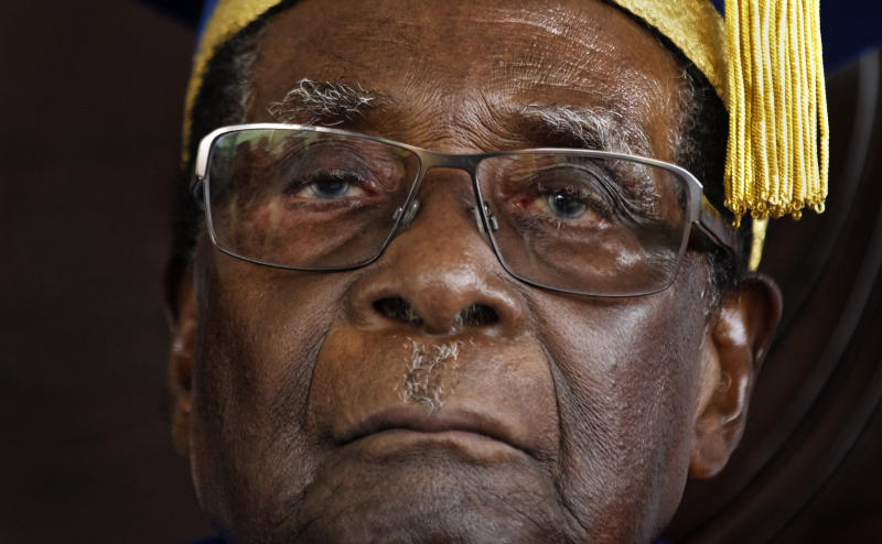 Zimbabwe's President Robert Mugabe sits for formal photographs with university officials, after presiding over a student graduation ceremony at Zimbabwe Open University on the outskirts of Harare, Zimbabwe Friday, Nov. 17, 2017. Mugabe made his first public appearance since the military put him under house arrest earlier this week. (AP Photo/Ben Curtis)