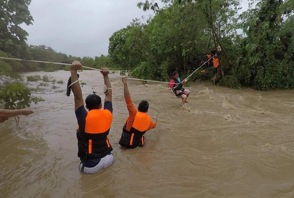 In this photo released by the Gonzaga Municipal Disaster Risk Reduction and Management Office, a resident is pulled along a rope as rescuers wait on the other side of a swollen river caused by heavy rains from Tropical Storm Kompasu in Gonzaga town, Cagayan province, northern Philippines, Monday Oct. 11, 2021. A number of people have been killed and others were reported missing in landslides and flash flood set off by a storm that barreled through the tip of the northern Philippines overnight then blew away Tuesday, officials said. (Gonzaga MDRRMO via AP)