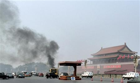 Vehicles travel along Chang'an Avenue as smoke raises in front of a portrait of late Chinese Chairman Mao Zedong at Tiananmen Square in Beijing