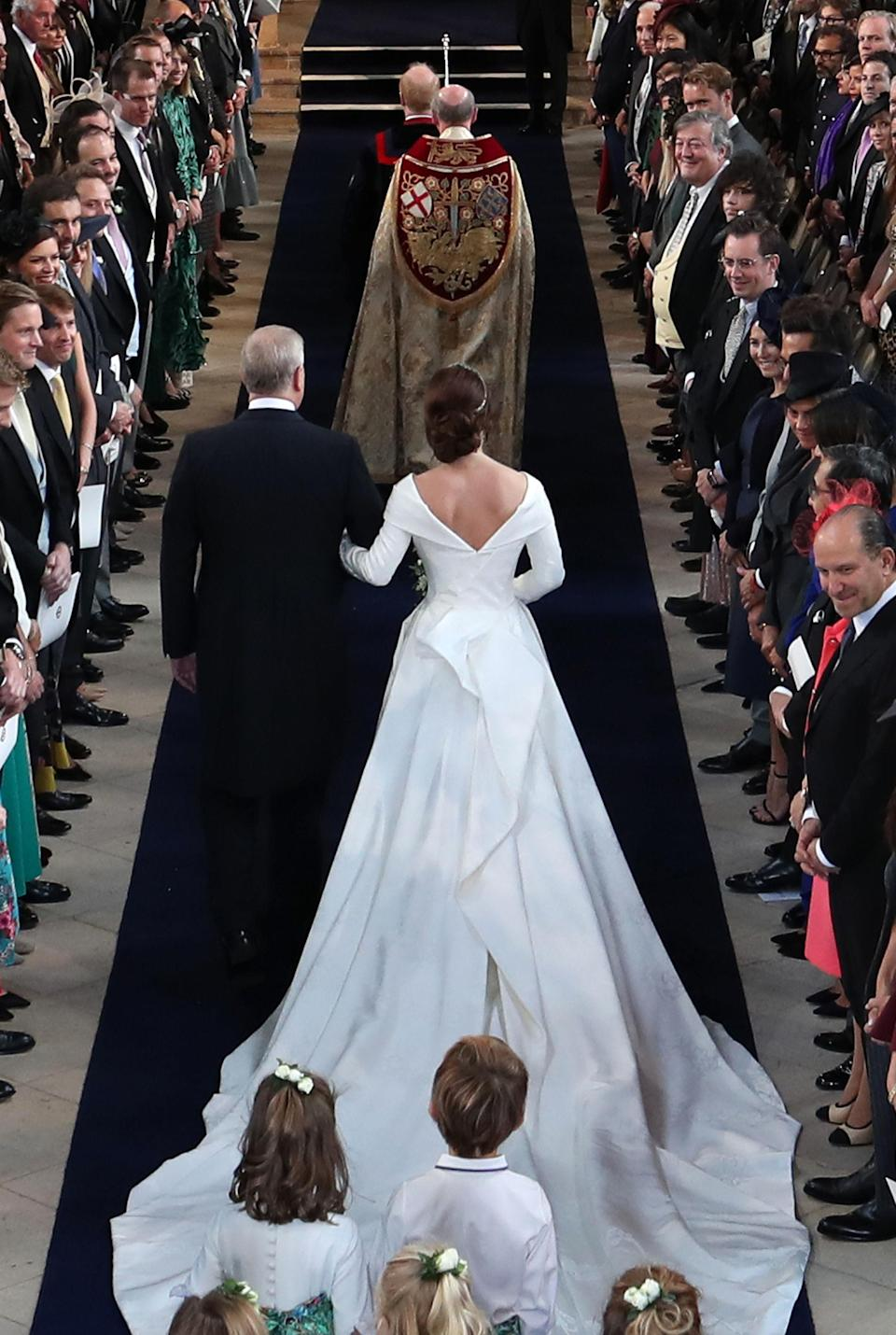 A closer look at Princess Eugenie's wedding gown as she walks down the aisle at St George's Chapel [Photo: PA]