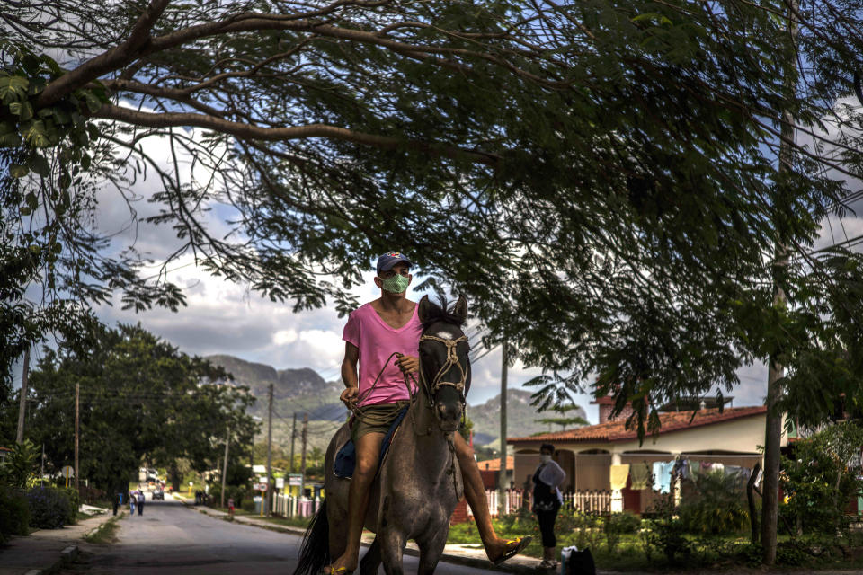 A man rides his horse through Viñales, Cuba, March 1, 2021. Both U.S. sanctions meant to punish the government and a COVID-19 pandemic have squashed tourism almost everywhere, making some Cubans hope that new U.S. President Joe Biden will reverse at least some of the restrictions implemented by his predecessor. (AP Photo/Ramon Espinosa)