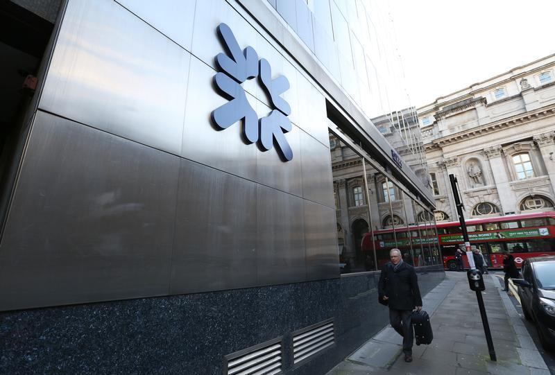 A man walks past a Royal Bank of Scotland building in central London