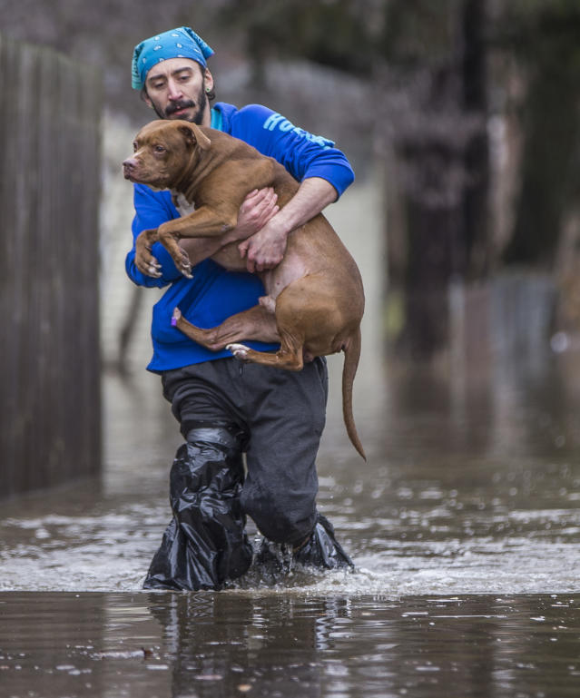 <p>Lance Lawson carries his dog Kawi, a 9-year-old pitbull, away from his flooded home Wednesday, Feb. 21, 2018, in South Bend, Ind. (Photo: Robert Franklin/South Bend Tribune via AP) </p>