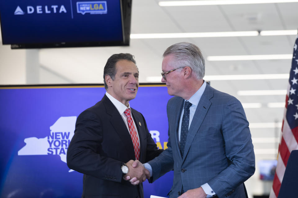 New York Governor Andrew Cuomo, left, and Delta Air Lines' CEO Ed Bastian shake hands during a ceremony at the new $3.9 billion Terminal C at LaGuardia Airport, Tuesday, Oct. 29, 2019, in New York. Cuomo said the progress at the airport contradicts naysayers who thought it would be impossible to rebuild the airport while still using it. (AP Photo/Mark Lennihan)
