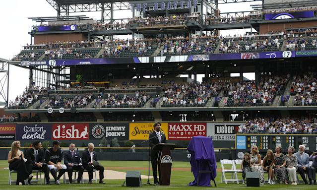 Retired Colorado Rockies first baseman Todd Helton, center, addresses the crowd during a ceremony to retire his playing number before the Rockies host the Cincinnati Reds in a baseball game in Denver on Sunday, Aug. 17, 2014. (AP Photo/David Zalubowski)