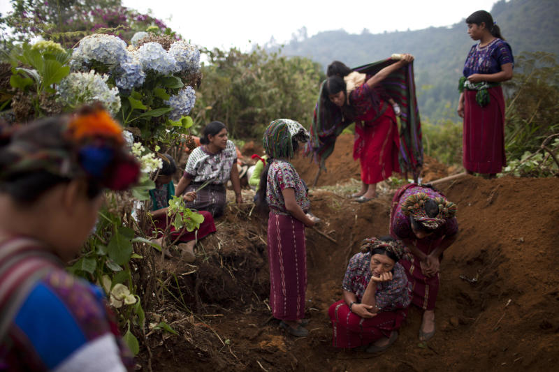 In this May 24, 2013 photo, Ixil Mayan women gather around a mass grave as forensic anthropologists exhume the skeletons of their loved ones who died during the country's civil war, near Ixtupil, Guatemala. Forensic experts continue to exhume bodies from clandestine graves. Lesser known are the mass graves that the Ixil dug to bury loved ones who died of starvation and hypothermia, while they hid in the mountains from the soldiers who razed their villages and killed thousands in the 1980s. (AP Photo/Rodrigo Abd)