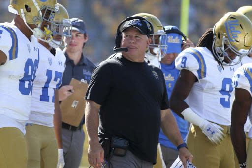 FILE - In this Nov. 10, 2018, file photo, UCLA head coach Chip Kelly, center, walks with his players prior to an NCAA college football game against Arizona State, in Tempe, Ariz. Chip Kelly isnt a fan of momentum and how it can impact a team, but the UCLA coach admitted that the Bruins performance over the second half of last season, that included a win over crosstown rival USC, provided a boost coming into this year. (AP Photo/Ralph Freso, File)