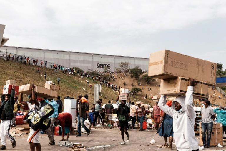Suspected looters carry goods from the Game Warehouse in Durban