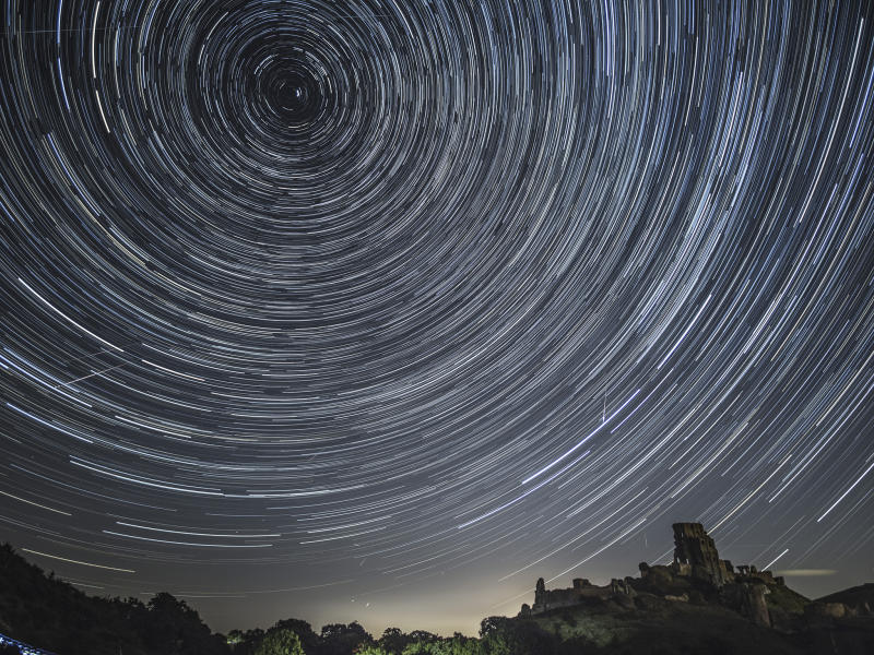 Comets streak across the night sky beneath stars that appear to rotate in a long-exposure photograph taken above Corfe Castle on August 12, 2016 in Corfe Castle in Dorset: Getty
