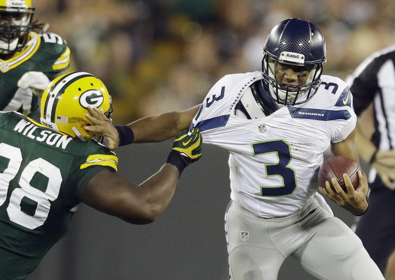 Seattle Seahawks quarterback Russell Wilson tries to get away from Green Bay Packers' C.J. Wilson during the second half of an NFL preseason football game Friday, Aug. 23, 2013, in Green Bay, Wis. (AP Photo/Jeffrey Phelps)