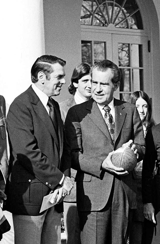 """FILE - In this Jan. 2, 1973, file photo President Richard Nixon, holds a souvenir football he received after the previous bowl game, and Washington Redskins coach George Allen appear in the White House Rose Garden to celebrate Redskins win over Dallas for the National Football Conference title. The NFL, which is trying to maintain its TV blackout of home games that don't sell out, missed an opportunity 40 years ago to keep an even more restrictive policy in place when it rebuffed an effort by Nixon to at least televise playoff games. Nixon gave his attorney general a message for NFL commissioner Pete Rozelle: """"If you make the move, for these playoff games, we will block any, any, legislation to stop anything else. I will fight it personally and veto any, any, legislation,"""" he said. (AP Photo/File)"""
