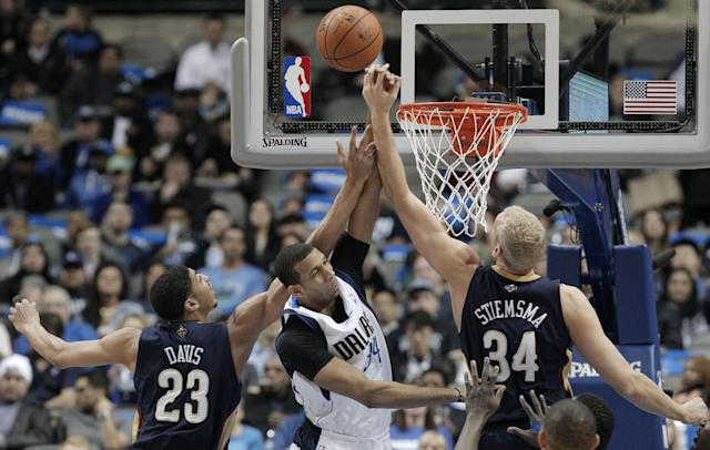 Dallas Mavericks' forward Brandan Wright, center, battles New Orleans Pelicans' Anthony Davis (23) and Greg Stiemsma, right, for a rebound during the first half of an NBA basketball game on Wednesday, Feb. 26, 2014, in Dallas. (AP Photo/Brandon Wade)
