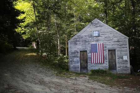 A U.S. flag hangs on the Friends School House in Weare, New Hampshire September 8, 2014, one day before the state's primary election. REUTERS/Brian Snyder
