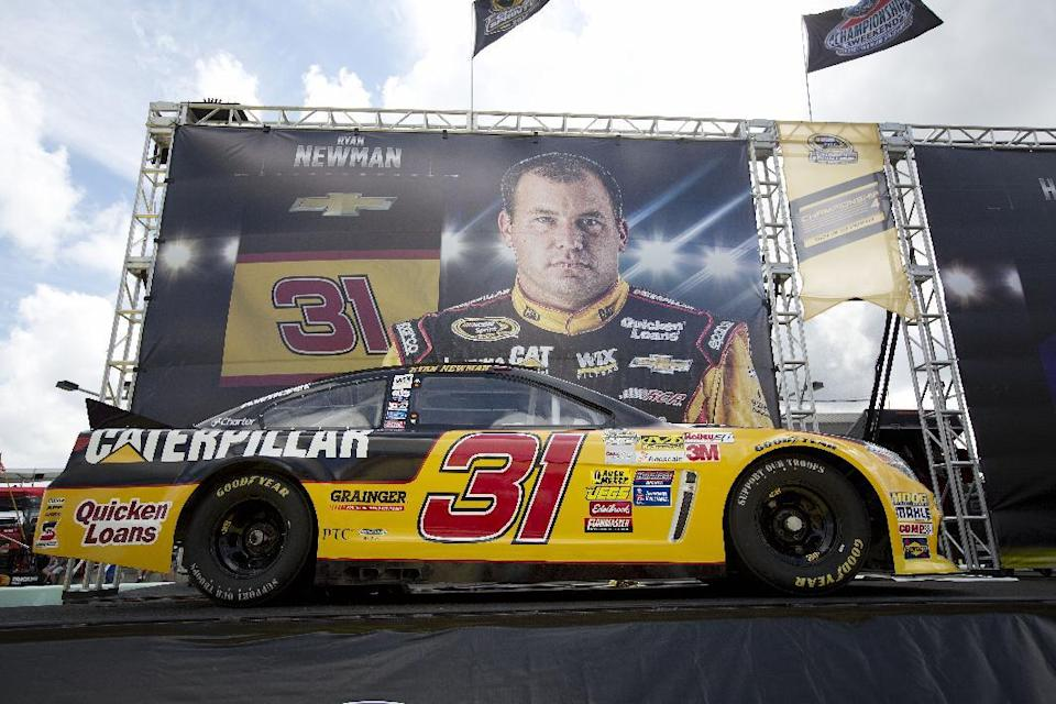 One of Ryan Newman's race cars sits in front of a bigger-than-life poster before the NASCAR Sprint Cup championship series auto race, Sunday, Nov. 16, 2014, in Homestead, Fla. (AP Photo/J Pat Carter)