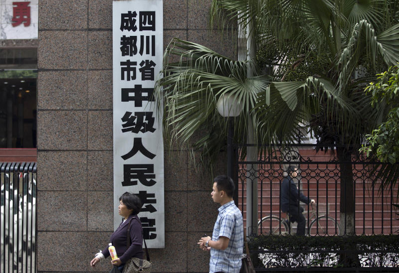 UPDATING THE CAPTION WHEN THE TRIAL STARTED - People walk past the Chengdu Intermediate People's Court in Chengdu in southwest China's Sichuan province Monday, Sept. 17, 2012. The trial of Wang Lijun, an ex-police chief at the center of China's worst political scandal in decades, started unexpectedly Monday, a day earlier than the court in the central city of Chengdu had announced. At the height of his career, Wang led a police crackdown on the violent underworld in a sprawling metropolis, arresting hundreds of gangsters and government officials, some of whom were sentenced and executed in a matter of months. Now the former police chief is in the hands of the opaque Chinese justice he once brandished against others. (AP Photo/Andy Wong)