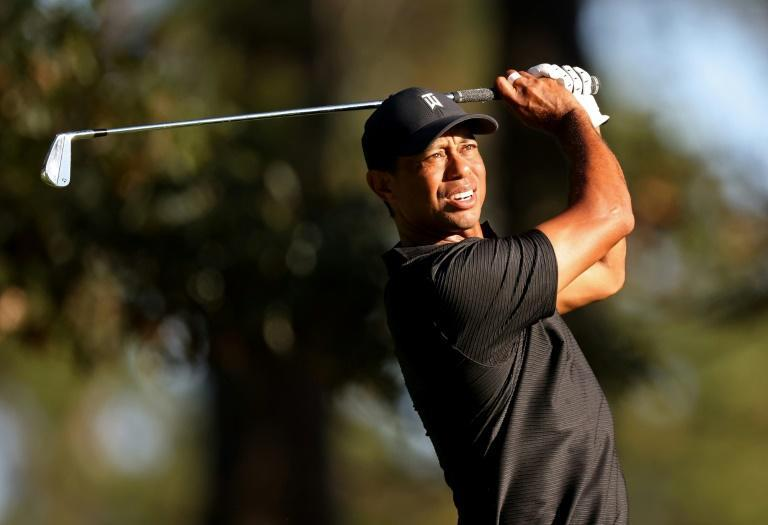 Defending champion Tiger Woods returned to action Saturday at Augusta National to complete the final eight holes of his darkness-halted second round at the Masters