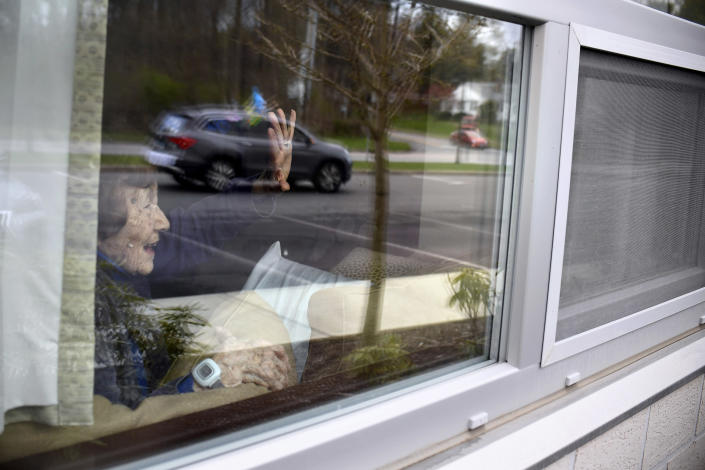 A resident at Jewish Senior Services in Bridgeport, Conn., waves to family from her window on Friday, May 1, 2020. (Jessica Hill for the New York Times)