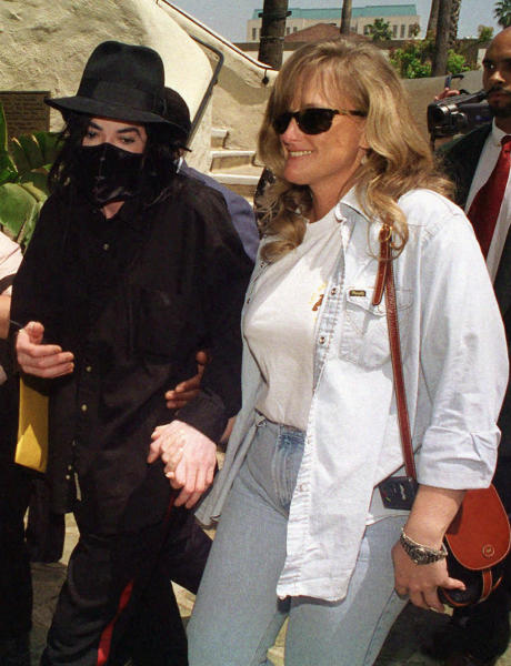 FILE - This April 28, 1996 file photo shows pop singer Michael Jackson, left, and his wife, Debbie Rowe, in Pasedena, Calif. Rowe told a Los Angeles jury on Thursday Aug. 15, 2013, that injuries and medical conditions left the singer feeling disfigured and forced him to wear wigs and de-pigment his skin. These difficult treatments she said were made harder by Jackson's superstar status. (AP Photo/Chris Pizzello, file)
