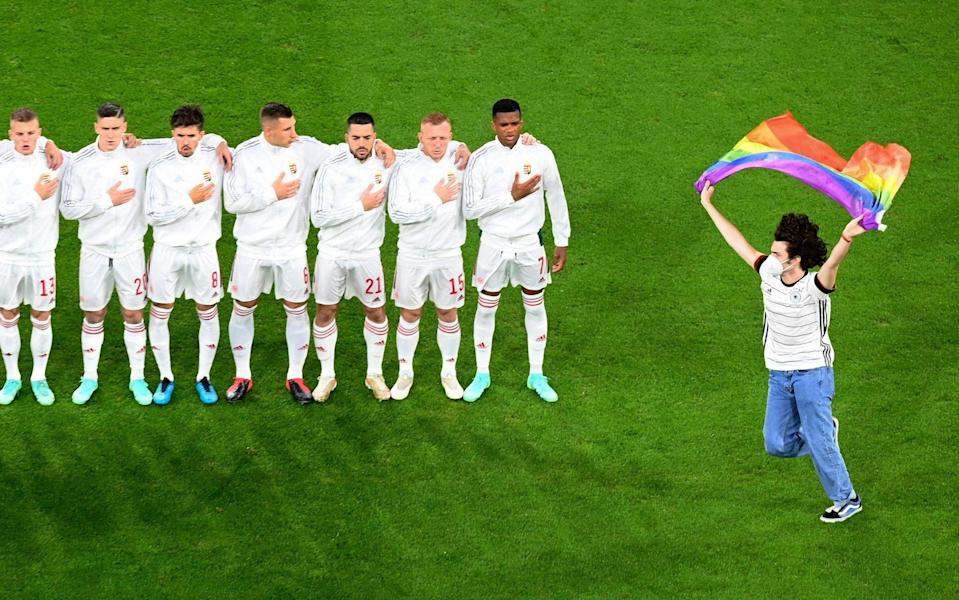 A protestor holding a rainbow flag runs onto the pitch in front of the Hungarian team before the Euro 2020 soccer championship group F match between Germany and Hungary at the football arena stadium in Munich - POOL GETTY