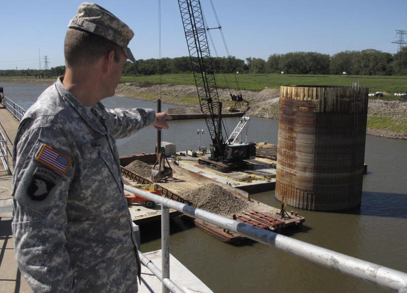 """FILE - In this Sept. 19, 2012 file photo, U.S. Army Corps of Engineers Col. Chris Hall points to a vertical, rock-filled steel tube called a """"protector cell"""" that serves as a buffer that Mississippi River barges rub against, aligning them before they actually enter the lock in Granite City, Ill. Emergency repairs are under way on that structure after workers discovered that an unarmored portion of it exposed by river levels dramatically lowered by the drought split open, spilling much of the rock into the channel and forcing the channel to be closed to shipping. The Mississippi River's 70-year-old system of locks and dams urgently needs upgrades to accommodate barges that have gotten bigger over time, a group of federal lawmakers is warning after last week's dayslong shutdown of the river's busiest lock.   (AP Photo/Jim Suhr)"""