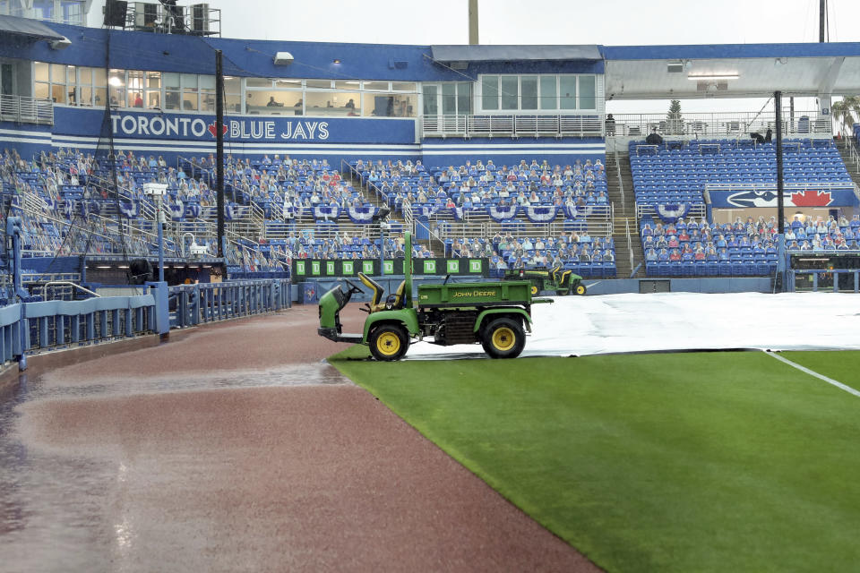 Rain delays the start of the baseball game between the Los Angeles Angels and Toronto Blue Jays Sunday, April 11, 2021, in Dunedin, Fla. (AP Photo/Mike Carlson)