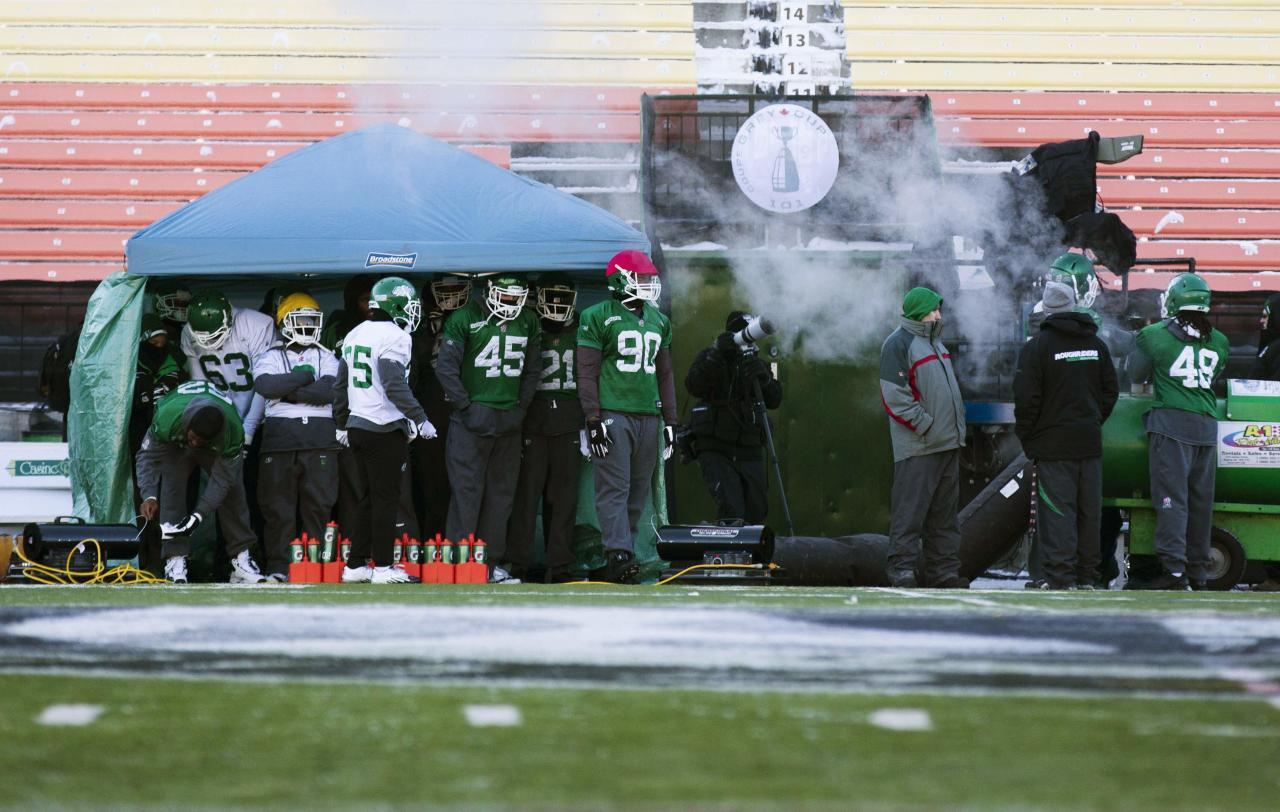 Saskatchewan Roughriders players stand under a heated tent during practice in Regina, Saskatchewan, November 22, 2013. The Saskatchewan Roughriders will play against the Hamilton Tiger-Cats in the CFL's 101st Grey Cup in Regina. REUTERS/Mark Blinch (CANADA - Tags: SPORT FOOTBALL)