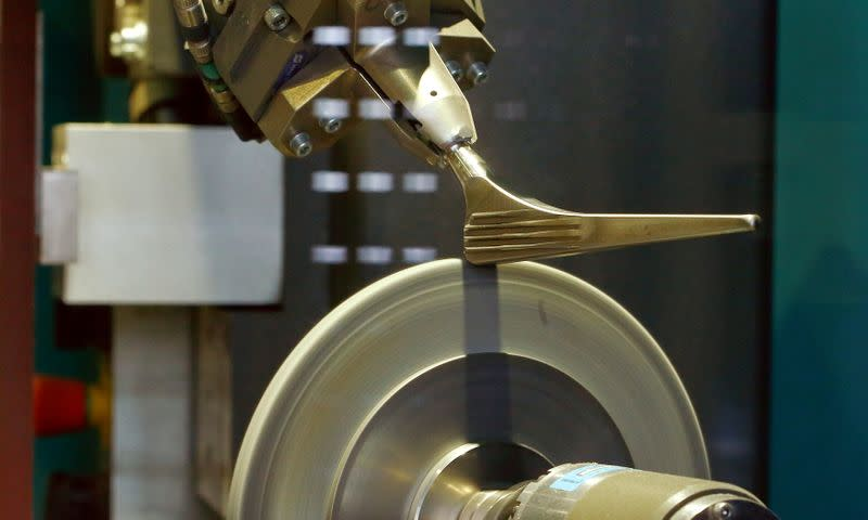 FILE PHOTO: A robot grinds a medical implant at a plant of medical implants maker Zimmer Biomet in Winterthur