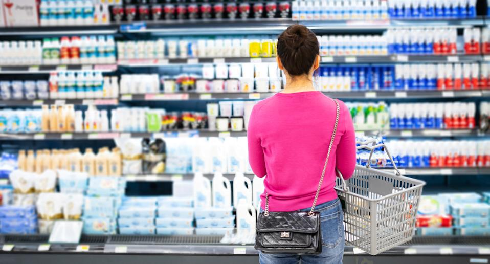 A person deciding which milk to purchase at the supermarket