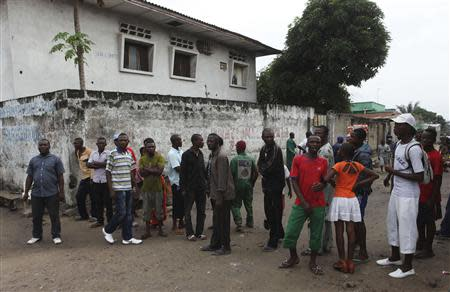 Residents gather to watch as security forces patrol the street near the state television headquarters in the capital Kinshasa, December 30, 2013. REUTERS/Jean Robert N'Kengo