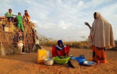 Zeinab, 14, (C) washes dishes as her mother Abdir Hussein gestures and her nephews play at a camp for internally displaced people from drought hit areas in Dollow, Somalia April 3, 2017. REUTERS/Zohra Bensemra