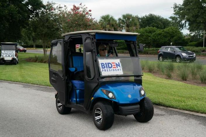 Casey Marr, a retiree from New Jersey drives his golf cart with a Biden for president sign after staging a daily protest against President Donald Trump in Orlando, Florida on July 23, 2020