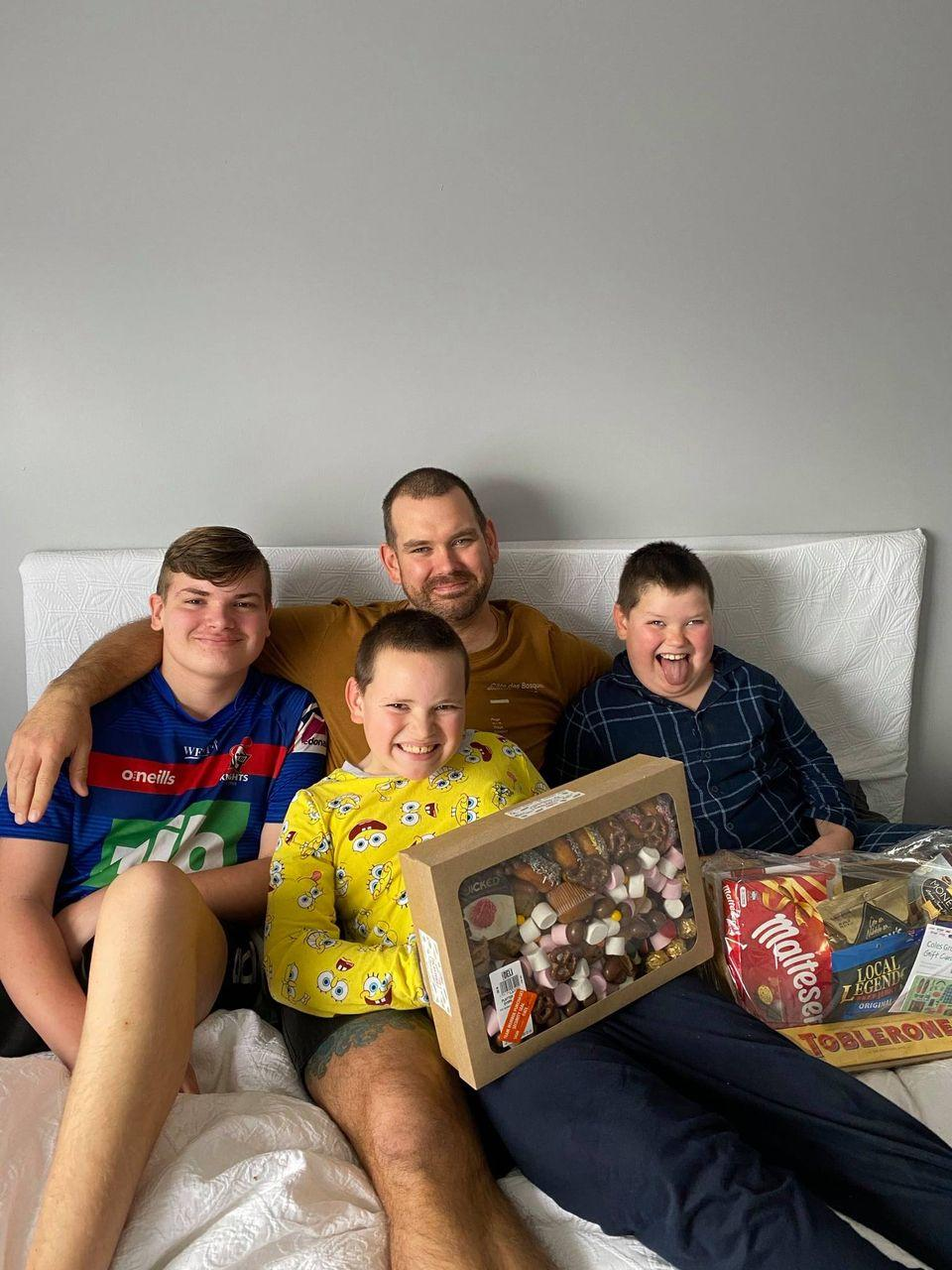 Father & 4 sons sitting on a bed with 2 gift packs. Source: Facebook