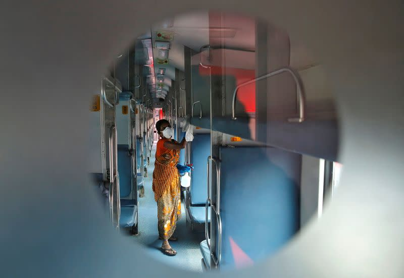 A worker disinfects the interiors of a passenger train parked at a railway yard as a preventive measure against coronavirus, on the outskirts of Kolkata