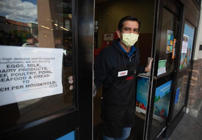 """A Ralphs employee stands at the door of the grocery store in Westchester, letting in only a few shoppers at a time. <span class=""""copyright"""">(Jason Armond/Los Angeles Times)</span>"""