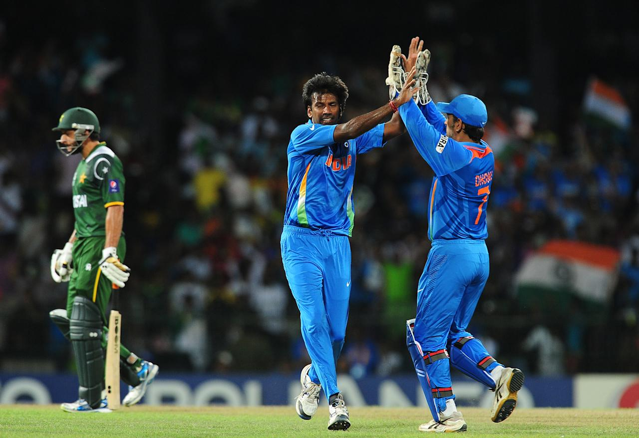 Indian cricketer Lakshmipathy Balaji (C) celebrates with captain and wicketkeeper Mahendra Singh Dhoni (R) after he dismissed Pakistan batsman Shahid Afridi (L)during the ICC Twenty20 Cricket World Cup's Super Eight match between India and Pakistan at the R. Premadasa International Cricket Stadium in Colombo on September 30, 2012. AFP PHOTO/ LAKRUWAN WANNIARACHCHI